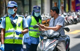 Maldives Police Service verifying an individual for permits during the travel restrictions and curfew imposed in the Greater Male' Region amid the ongoing COVID-19 outbreak in the country. PHOTO: NISHAN ALI / MIHAARU