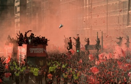 (FILES) In this file photo taken on June 2, 2019 football fans line the streets to see the Liverpool football team take part in an open-top bus parade around Liverpool, north-west England after winning they won the UEFA Champions League final football match between Liverpool and Tottenham. - AFP photographer Oli Scarff won third prize, in the Sports-Singles category in the World Press Photo (WPP) contest on April 16, 2020. (Photo by Oli SCARFF / AFP)