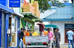 Expatriate workers unloading goods from a pick-up at the local market area. PHOTO: MIHAARU