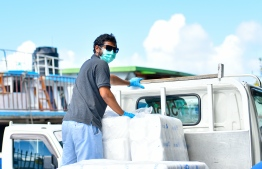A worker, clad in gloves and a mask, handles deliveries of goods meant to circulate amongst residents of Maldives. Dozens like him work tirelessly in the unforgiving April sun to ensure that other frontline workers, ordinary residents, across the archipelago receive the supplies they need. PHOTO: AHMED AWSHAN ILYAS / MIHAARU