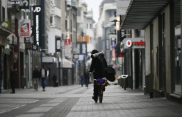 A man cycles through an empty pedestrian area in Cologne, western Germany, on April 19, 2020, amid the novel coronavirus COVID-19 pandemic. (Photo by Ina FASSBENDER / AFP)