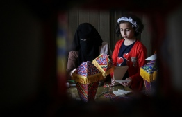 Members of the Palestinian al-Yaqoubi family gather around a table during the novel coronavirus lockdown, to make lanterns to sell ahead of the Muslim holy month of Ramadan, in Khan Yunis, in the southern Gaza Strip on April 15, 2020. (Photo by SAID KHATIB / AFP)