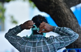 A person putting on a facemask in public. PHOTO: MIHAARU