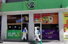 Persons covered in protective gear, entering local supermarket 'VB Mart' to disinfect and clean the property. PHOTO: MIHAARU