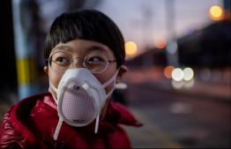 A child wearing a protective mask in Beijing. Those going out in public without wearing one will be fined as the city tightens regulations to ensure hygiene. PHOTO: AFP
