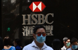 Pedestrians wear face masks as they walk past HSBC signage outside a branch of the bank in Hong Kong on April 28, 2020. - HSBC on April 28 said first quarter pre-tax profits almost halved as the banking giant was battered by the global coronavirus pandemic while it embarked on a major restructuring. (Photo by Anthony WALLACE / AFP)