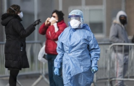 (FILES) In this file photo a medical worker at the NYC Health Hospital is seen in front of the COVID-19 testing site on April 22, 2020 in the Queens borough of New York City. - Almost half of New Yorkers knew someone who died of the new coronavirus, according to a poll April 27, 2020 which found overwhelming support for confinement measures opposed elsewhere in America.  More than 16,000 New York City residents are thought to have succumbed to COVID-19, out of at least 153,000 confirmed infections, since the Big Apple declared its first case in early March. (Photo by Johannes EISELE / AFP)