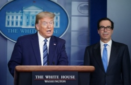 US President Donald Trump speaks as Treasury Secretary Steven Mnuchin listens during the daily briefing on the novel coronavirus, COVID-19, in the Brady Briefing Room of the White House in Washington, DC on April 21, 2020. (Photo by MANDEL NGAN / AFP)