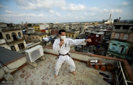 (FILES) In this file photo taken on April 07, 2020 Cuban Alejandro Lopez trains martial arts on the rooftop of his home in Havana on April 7, 2020. - Due to the social isolation caused by COVID-19, many athletes excercise at home. Cuba has 350 cases of the new coronavirus. Some neighborhoods are quarantined, and more than 6,000 tourists who are still in the island remain isolated in hotels. (Photo by YAMIL LAGE / AFP)