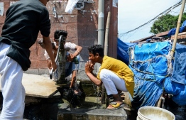 """In this picture taken on May 4, 2020 Muslim youths perform ablutions before conducting prayers in a closed market area during a government-imposed nationwide lockdown to prevent the spread of the COVID-19 coronavirus in New Delhi. - India's 200 million Muslims have long complained of growing hostility since the Hindu nationalist Prime Minister Narendra Modi came to power in 2014. But the COVID-19 coronavirus pandemic added a new dimension, turning Muslims into the new """"untouchables"""", a word usually used to refer to India's lowest castes. (Photo by Sajjad HUSSAIN / AFP) /"""