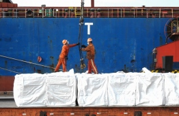 Workers upload plywood that will be exported on a cargo ship at a port in Lianyungang in China's eastern Jiangsu province on May 7, 2020. - China's exports saw a shock 3.5 percent rise in April despite the global impact of the coronavirus pandemic, official figures showed on May 7, partly due to rising medical exports. (Photo by STR / AFP) /