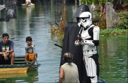 Local youth representatives dressed as a Stormtrooper and Darth Vader from the Star Wars film franchise patrol in a wooden boat around a submerged village to remind residents to stay at home during the enhanced community quarantine in suburban Manila on May 6, 2020, as part of government's efforts to combat the spread of the COVID-19 coronavirus. PHOTO: AFP