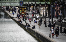People walk along the Canal de l'Ourcq in Paris on May 8, 2020, on the 53rd day of a lockdown in France aimed at curbing the spread of COVID-19, caused by the novel coronavirus.  Christophe ARCHAMBAULT / AFP