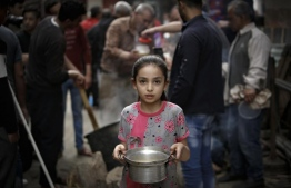 On April 24, 2020, in Gaza City, a Palestinian girl carries a portion of soup, given out to families in need during the Islamic holy month of Ramadan, amid the coronavirus COVID-19 pandemic. PHOTO: UNICEF