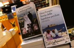 """(FILES) In this file photo taken on October 04, 2016 shows books by Italian writer Elena Ferrante in a bookstore in Rome. - Netflix announced May 12, 2020, it will adapt the new novel from Italian writer Elena Ferrante, """"The Lying Life of Adults,"""" into a television series, even though the book won't be translated into English until September. (Photo by GABRIEL BOUYS / AFP)"""