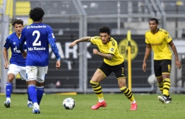 Dortmund's English midfielder Jadon Sancho vies for the ball during the German first division Bundesliga football match BVB Borussia Dortmund v Schalke 04 on May 16, 2020 in Dortmund, western Germany as the season resumed following a two-month absence due to the novel coronavirus COVID-19 pandemic. (Photo by Martin Meissner / POOL / AFP) / DFL REGULATIONS PROHIBIT ANY USE OF PHOTOGRAPHS AS IMAGE SEQUENCES AND/OR QUASI-VIDEO