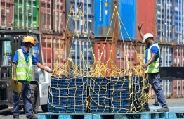 Workers unloading shipments at Male' Commercial Harbour. PHOTO: MIHAARU