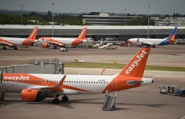 Easyjet aircraft stand on the apron the departure gates at Manchester Airport in Manchester, northern England on May 11, 2020, where they have begun a trial of body temperature screening during the COVID-19 pandemic. - Prime Minister Boris Johnson has announced plans to quarantine people arriving in Britain by air for 14 days to prevent new COVID-19 infections from abroad, under a phased lockdown easing that seeks to avoid a second spike. (Photo by Oli SCARFF / AFP)