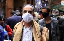 A man walks while clad in mask due to the COVID-19 coronavirus pandemic along an alley at an open-air market in Yemen's capital Sanaa on May 20, 2020, as Muslims shop ahead of the Eid al-Fitr holiday marking the end of the holy fasting month of Ramadan. (Photo by Mohammed HUWAIS / AFP)