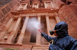 (FILES) In this file photo taken on March 17, 2020, a labourer sprays disinfectant in Jordan's archaeological city of Petra south of the capital Amman on March 17, 2020, to prevent the spread of COVID-19. - The International Monetary Fund on May 21, 2020, approved $396 million for Jordan to fight the coronavirus pandemic, a disbursement equal to about a quarter of its projected need amid the global economic downturn. (Photo by Khalil MAZRAAWI / AFP)