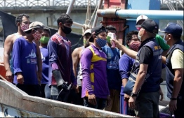 Immigration officers check the temperatures of Myanmar fisherman, as a preventive measure against the spread of the COVID-19 novel coronavirus, at the port in Pattani on April 11, 2020. (Photo by Tuwaedaniya MERINGING / AFP)