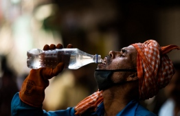 A labourer quenches his thirst with water from a bottle on a street amid rising temperatures in New Delhi on May 27, 2020. - India is wilting under a heatwave, with the temperature in places reaching 50 degrees Celsius (122 degrees Fahrenheit) and the capital enduring its hottest May day in nearly two decades. (Photo by Jewel SAMAD / AFP)