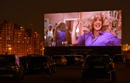 """Cinema-goers in their cars attend a screening of the US musical romantic comedy film """"Grease"""" during the reopening of the Autocine Madrid Race drive-in cinema, on May 27, 2020 in Madrid, as Spain eases lockdown measures taken to curb the spread of the COVID-19 disease caused by the novel coronavirus. - For many, it was a long-awaited chance to feel normal again, sitting in their cars belting out """"Summer Nights"""" at Madrid's drive-in cinema on a rare night out after a 10-week lockdown. (Photo by Gabriel BOUYS / AFP)"""
