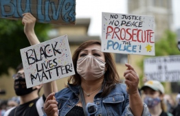 Protesters hold signs during a Black Lives Matter protest against police brutality and racism in the US, including the recent deaths of George Floyd, Ahmaud Arbery, Breonna Taylor, in Boston, Massachusetts, on May 29, 2020. - The Minneapolis police officer accused of killing George Floyd, a handcuffed African American man, was charged with murder on May 29 as authorities declared a curfew after three nights of violent protests left parts of the city in flames. (Photo by Joseph Prezioso / AFP)
