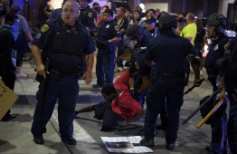 """A protester is detained by police during a """"Justice 4 George Floyd"""" demonstration over the death of George Floyd, a black man who died after a white policeman kneeled on his neck for several minutes in Houston, Texas on May 29, 2020. - Demonstrations are being held across the US after George Floyd died in police custody on May 25. (Photo by Mark Felix / AFP)"""