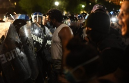 Protesters face off with police outside the White House in Washington, DC, early on May 30, 2020 during a demonstration over the death of George Floyd, a black man who died after a white policeman kneeled on his neck for several minutes. - Violent protests erupted across the United States late on May 29 over the death of a handcuffed black man in police custody, with murder charges laid against the arresting Minneapolis officer failing to quell boiling anger. (Photo by Eric BARADAT / AFP)