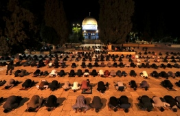 Palestinians perform the dawn prayer (salat al-fajr) inside the Al-Aqsa mosque compound, Islam's third holiest site, in Jerusalem's Old City on May 31, 2020, after being closed for over two months because of the coronavirus pandemic. (Photo by AHMAD GHARABLI / AFP)