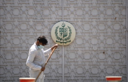 """A man sweeps in front of the main gate of the Pakistan High Commission in New Delhi on June 1, 2020. - Two officials at the Pakistan High Commission in New Delhi were being expelled for """"indulging in espionage activities"""", India's foreign ministry said late on May 31, with tensions already heightened between the nuclear-armed rivals. The South Asian neighbours have a long-running dispute over Kashmir, which was split between them in 1947 when they gained independence from Britain. (Photo by Sajjad HUSSAIN / AFP)"""