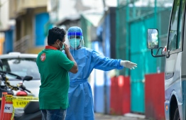 A frontline worker collecting random samples on the streets of Malé City. PHOTO: MIHAARU