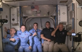 This NASA video frame grab image shows NASA SpaceX's Crew Dragon astronauts Douglas Hurley(R) and Robert Behnken(2ndR) arriving after the hatch opened to the International Space Station posing with other astronauts on May 31, 2020. US astronauts on a SpaceX Crew Dragon capsule were completing final close out procedures before entering the International Space Station after the hatch was opened between the two vessels. The hatch opened at 1:02 pm Eastern Time (1702 GMT) as Bob Behnken and Doug Hurley were poised to cross over into the station, the first US astronauts to arrive on an American spacecraft in nine years. PHOTO/AFP