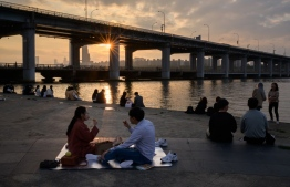 In a photo taken on May 24, 2020, people sit before the city skyline and Han river in a park in Seoul. (Photo by Ed JONES / AFP)