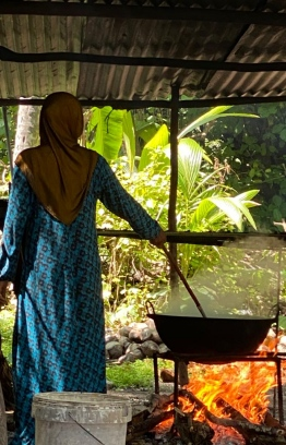 A woman pictured cooking on a traditional 'dharu undhun', using firewood. PHOTO/UTHEMA