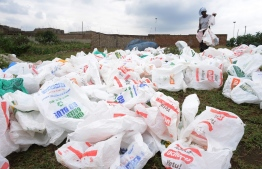 (FILES) In this file photo taken on June 24, 2014 a woman sort out plastic bags after washing them for re-use at the shores of a river in Nairobi. - Kenya on World Environment Day barred all single-use plastics such as water bottles and straws from its national parks, beaches, forests and other protected areas. The implementation of the ban, first announced a year ago, was ordered in a letter from Tourism Minister Najib Balala last week. (Photo by Simon MAINA / AFP)