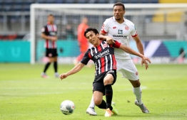 Frankfurt's Japanese midfielder Makoto Hasebe (L) and Mainz' Austrian forward Karim Onisiwo vie for the ball during the German first division Bundesliga football match Eintracht Frankfurt v 1. FSV Mainz 05 on June 6, 2020 in Frankfurt am Main, western Germany. (Photo by Alexander HASSENSTEIN / POOL / AFP) / DFL REGULATIONS PROHIBIT ANY USE OF PHOTOGRAPHS AS IMAGE SEQUENCES AND/OR QUASI-VIDEO