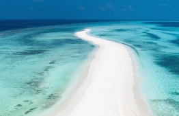 An aerial view of a winding stretch of beach, pearly white-sand pathway leading into the gradient of blues - and image that is deeply associated with Maldives. PHOTO: VISIT MALDIVES