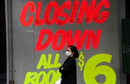"A woman walks past a closing down sign on an empty shop in Melbourne's central business district on June 3, 2020. - Australia is heading for its first recession in nearly three decades after the economy shrunk in the January-March quarter, with a ""far more severe"" reading expected in the next three months as the effects of the virus shutdown bite. (Photo by William WEST / AFP)"