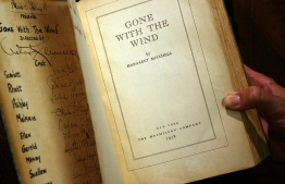 "(FILES) In this file photo a copy of the book ""Gone With the Wind"" by Margaret Mitchell, signed by producer, director, and most of speaking cast of the 1939 Hollywood film, is pictured 18 October 2007 in Los Angeles. - ""Gone with the Wind"" was removed from the HBO Max streaming platform June 9, as mass protests against racism and police brutality prompt television networks to reassess their offerings. PHOTO: GABRIEL BOUYS / AFP"