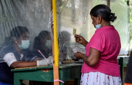 An election official (L) behind a plastic sheet checks the identification card of a voter during a mock election to test the guidelines implemented against the COVID-19 coronavirus in Ingiriya of Kalutara District in Western Province on June 14, 2020. (Photo by LAKRUWAN WANNIARACHCHI / AFP)