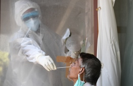 In this photograph taken on June 16, 2020, a health official collects a swab sample from a man to test for the COVID-19 coronavirus after authorities eased restrictions imposed as a preventive measure against the spread of the COVID-19 coronavirus, in New Delhi. - Early optimism that South Asia might have dodged the worst ravages of the coronavirus pandemic has disappeared as soaring infection rates turn the densely populated region into a global hot spot. After several months trailing the US and western Europe, cases of COVID-19 are surging across South Asia -- home to almost a quarter of the world's population -- where the virus is wreaking havoc on fragile medical systems and underfunded health agencies are pushed to breaking point. (Photo by Sajjad  HUSSAIN / AFP) /