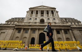 A pedestrian walks past the Bank of England in London on June 17, 2020. - The Bank of England, confronted by Britain's collapsing coronavirus-ravaged economy, will on June 18 reveal the outcome of its latest monetary policy meeting with analysts predicting more stimulus. The British central bank has been at the forefront of economic fire-fighting over this year's deadly COVID-19 emergency -- and could expand its quantitative easing (QE) stimulus in an attempt to kickstart growth. (Photo by Tolga Akmen / AFP)