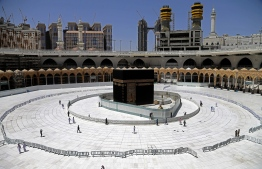 (FILES) In this file photo taken on April 3, 2020 Muslim worshippers walk around the sacred Kaaba in Mecca's Grand Mosque, Islam's holiest site, during the coronavirus Covid-19 pandemic. - Saudi Arabia is expected to scale back or call off this year's hajj pilgrimage for the first time in its modern history, a perilous decision as coronavirus cases spike. With the annual ritual in doubt, Muslim nations are pressing Riyadh to give its much-delayed decision on whether the hajj will go ahead as scheduled in late July. But as the kingdom negotiates a call fraught with political and economic risks in a tinderbox region, time is running out to organise logistics for one of the world's largest mass gatherings. PHOTO: AFP