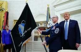 "(FILES) In this file photo taken on May 15, 2020, Gen. Jay Raymond (R), Chief of Space Operations presents US President Donald Trump with the official flag of the US Space Force in the Oval Office of the White House in Washington, DC. The US Space Force military wing revealed on June 30, 2020, that one of its units would be named ""Space Operations Command"" -- or ""SpOC"" for short, in an echo of pointy-eared ""Star Trek"" character Spock. An earnest statement from Space Force unveiled its organizational structure, but made no reference to SpOC's fictional predecessor who was the unflappable science officer on the Starship Enterprise. (Photo by MANDEL NGAN / AFP)"