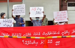 """Participants of """"Majlis Heylavvaa"""" protest organised by Navaanavai holding up banners and sign boards in front of the Parliament. PHOTO: AHMED AWSHAN ILYAS"""