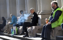 Workers take a break in the winter sun in Melbourne's central business district on June 17, 2020, as more Australians return to the city centre with a relaxing of the COVID-19 coronavirus rules. (Photo by William WEST / AFP)