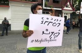 "Paticipant of Navaanavai's ""Majilis Heylavvaa"" protest holding a sign that reads ""Capitalist's Parliament"". PHOTO: NAVAANAVAI"