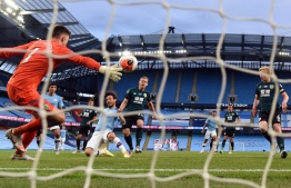 Manchester City's Spanish midfielder David Silva scores the fourth goal past Burnley's English goalkeeper Nick Pope during the English Premier League football match between Manchester City and Burnley at the Etihad Stadium in Manchester, north west England, on June 22, 2020. (Photo by Michael REGAN / POOL / AFP) / RESTRICTED TO EDITORIAL USE. No use with unauthorized audio, video, data, fixture lists, club/league logos or 'live' services. Online in-match use limited to 120 images. An additional 40 images may be used in extra time. No video emulation. Social media in-match use limited to 120 images. An additional 40 images may be used in extra time. No use in betting publications, games or single club/league/player publications. /